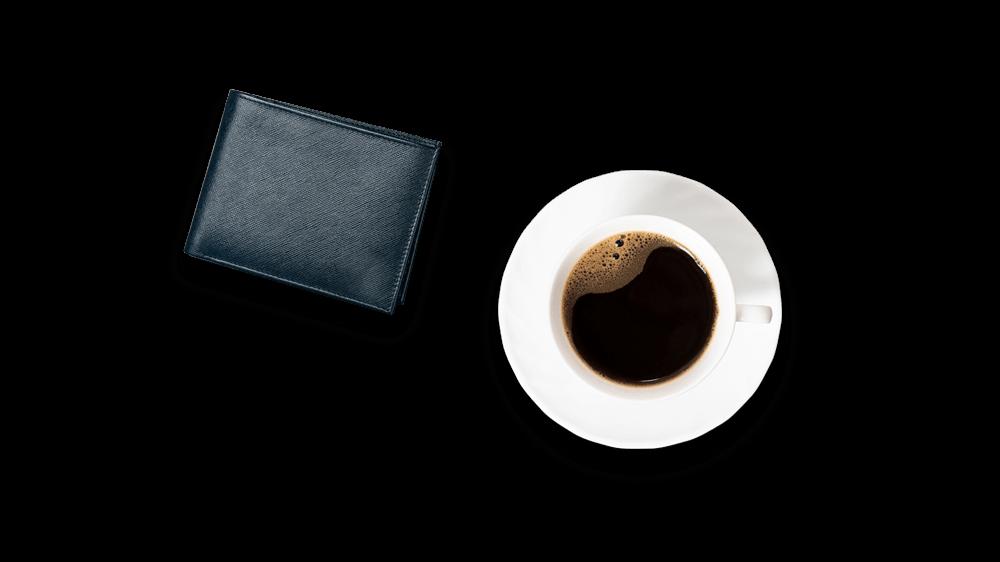 Tasse mit Brieftasche daneben