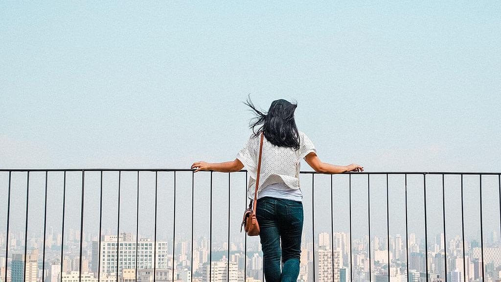 Person schaut über Geländer auf Stadt